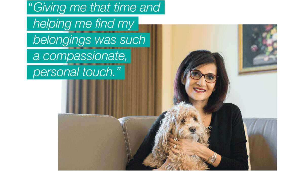 """A woman holding her dog on a couch, text on the image reads, """"Giving me that time and helping me find my belongings was such a compassionate, personal touch."""""""