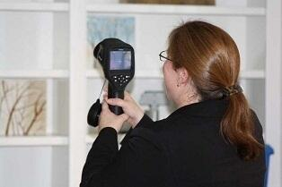 Sheila Courtney, senior risk manager for PURE Insurance, uses an infrared camera to search a new policyholder's home for cold spots that could indicate leaking. Homeowners who install a leak detection system can get a discount on their insurance rate.