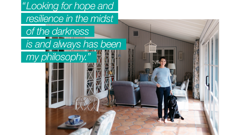 A PURE member standing barefoot, smiling in her high-end home with black her black lab beside her.